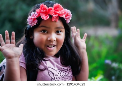 A pretty young native looking girl wearing a backpack and floral head band with hands up in the air, expressing an emotion of surprise.