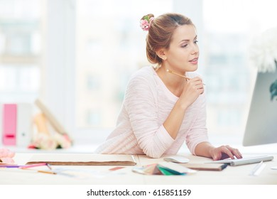 Pretty young owner of design firm writing e-mail to her business partner while sitting against panoramic window