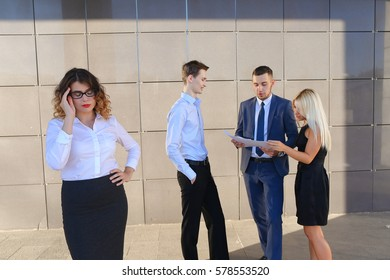 Pretty young perspective business woman, student holds on head from fatigue, rests, took break from work, holds paper and waving them, watching and stands on background of colleagues who discuss