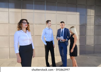 Pretty young perspective business woman, student rests, took break from work, holds paper and waving them, watching and stands on background of colleagues who discuss workflows, consider paper near of