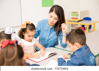 Pretty young preschool teacher helping her pupils with some writing assigment in the classroom