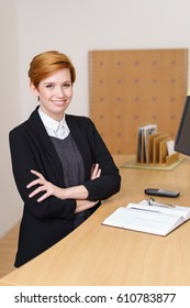 Pretty young receptionist with a welcoming smile standing with folded arms behind the reception desk of a corporate business or hotel