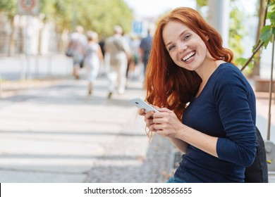 Pretty young redhead woman with a happy smile standing leaning on a low wall in a quiet urban street holding a mobile phone