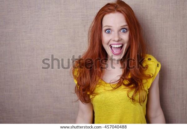 Mooie jonge roodharige vrouw met een gelukkige verrast uitdrukking van brede ogen genot staande tegen een beige achtergrond met kopieerruimte