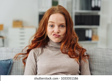 Pretty young redhead woman pulling a funny face making an exaggerated grimace with her lips as she sits on a sofa at home