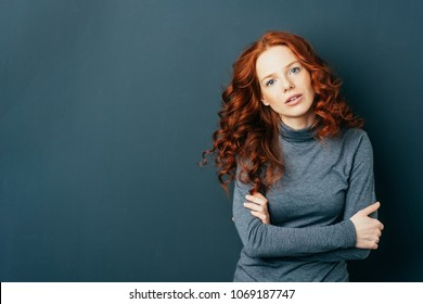 Pretty young redhead woman staring intently at the camera with folded arms and parted lips over a dark studio background with copy space