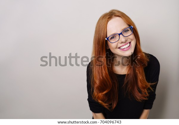 Pretty young redhead woman wearing glasses leaning forwards with a cute smile as she stares at the camera with copy space