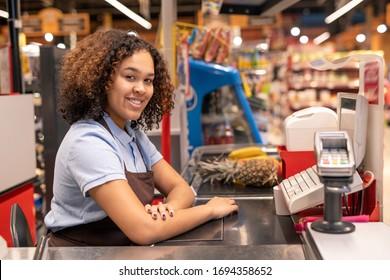 Joli jeune vendeur en tablier assis à la caisse dans un supermarché et vous regardant avec le sourire tout en servant les clients