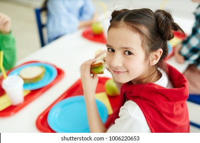 Pretty young schoolgirl eating sandwich at lunch break after classes