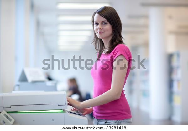 pretty young secretary using a copy machine (shallow DOF; color toned image)