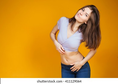 Pretty young sexy fashion sensual woman posing on yellow wall background dressed in hipster style jeans outfit.