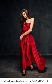 Pretty young sexy model female with dark hair in amazing long red dress and black shoes posing in dark studio