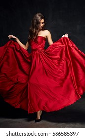 Pretty young sexy model female with dark hair in amazing long red draped dress and black shoes posing in dark studio