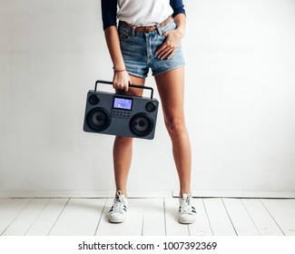 Pretty young sexy tanned girl posing in summer in white studio with hi-fi modern tape recorder