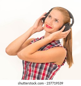 Pretty young sexy tanned girl posing  in studio with headphones and smile  listening music