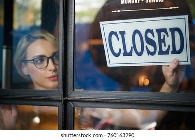 Pretty young shop owner turning closed sign