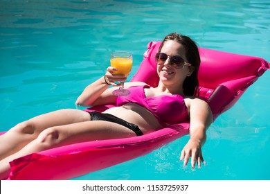 Pretty young slim woman lounging in a backyard swimming pool holding a mimosa in a glass relaxing in the sunshine. Woman in bikini on a pink raft in an outdoor swimming pool. Looking at camera.