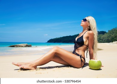 Pretty young slim woman on a beach near blue clean water on white sand
