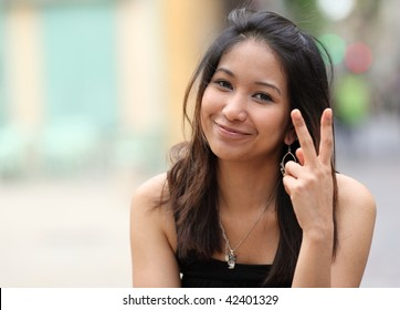 pretty young smiling asian woman on the street making the peace sign