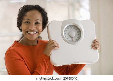 Pretty young smiling Beautiful African American woman holding scale