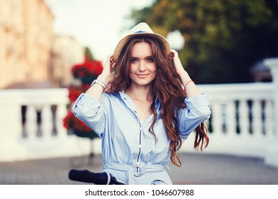 Pretty young smiling woman in hat outdoors