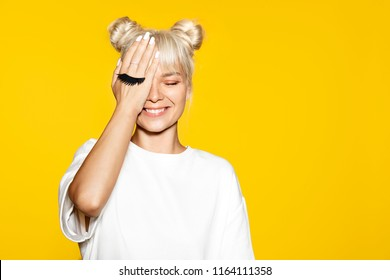 Pretty young smiling woman having fun with fake eyelash on yellow background. Model with blonde hair posing in studio. Concept of emotions.