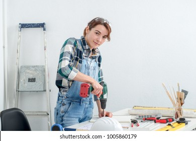 a pretty young smiling woman using cordless drill