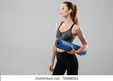 Pretty young sportswoman holding fitness mat while standing isolated over gray background