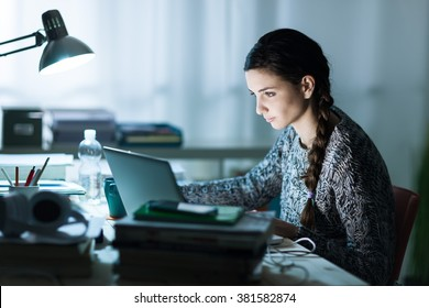 Pretty young student sitting at desk and doing her homework, she is connecting to the internet with a laptop