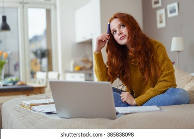 Pretty young student working at home on her laptop computer sitting on her bed staring thoughtfully into the air