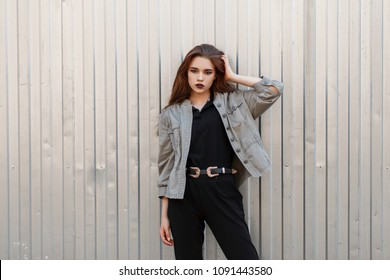 Pretty young stylish woman in a fashionable jacket and black T-shirt posing near a metal wall
