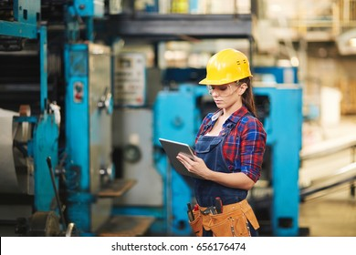 Pretty young technician in protective eyewear and hardhat inspecting machine and taking notes with help of digital tablet