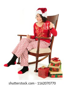 A pretty young teen lifting her mug for a Christmas toast.  She's wearing a Santa hat and pajamas and sits in a vintage rocking chair.