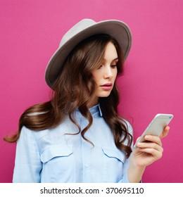 Hübsches junges Mädchen, das auf ihrem neuen modernen Handy auf rosafarbenem Hintergrund Textnachrichten tippt und liest