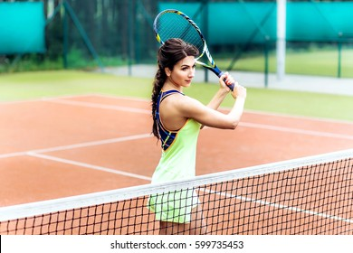 pretty young tennis player woman with long hair playing tennis. Female athlete wearing yellow sportswear