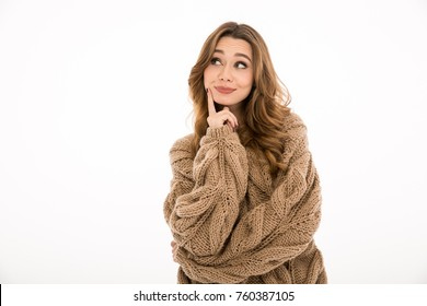Pretty young thinking lady dressed in warm sweater standing isolated over white wall background. Looking aside.