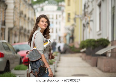 Pretty young tourist woman in casual clothes on a sidewalk of the street. Curly female on vacation in european city.