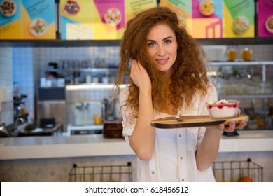 Pretty young waitress holding tray with dessert while standing in cafe