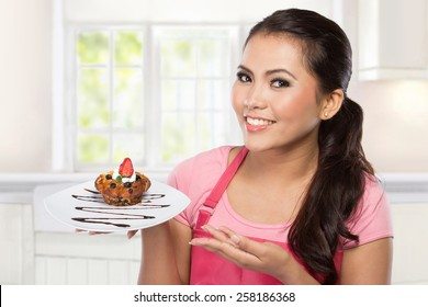 pretty young wife hold a plate of dessert and presenting
