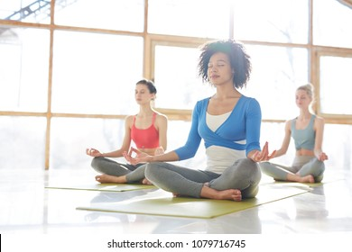 Pretty young woman in activewear and two more girls relaxing in gym or yoga center by large window