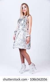 Pretty young woman in the aluminium foil clothes over grey background