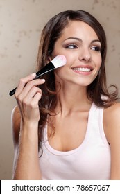 Pretty young woman applying cosmetic paint brush
