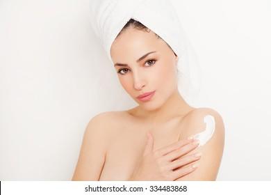 pretty young woman applying cream on her body, studio white