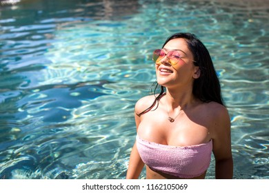Pretty young woman in aqua blue water wearing rainbow sunglasses