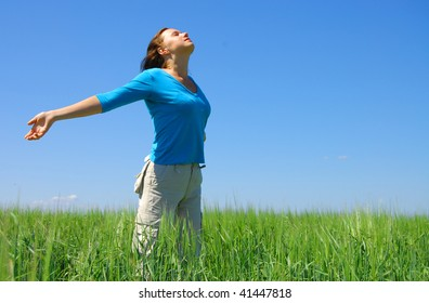 Pretty young woman with arms raised standing on Meadow