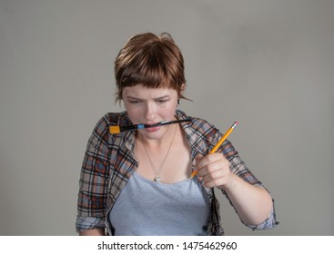 A pretty young woman artist holds a brush in her teeth and pencil in hand, while looking anguished as a result of artistic creative block as she stares down at her work..