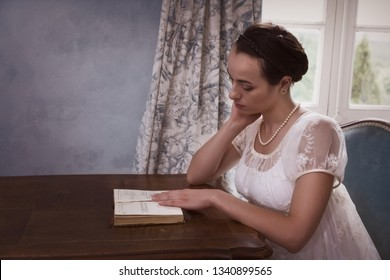 Pretty young woman in authentic regency dress reading a book in vintage room