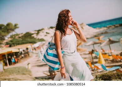 Pretty young woman with a bag using mobile phone on the beach at sunny summer day