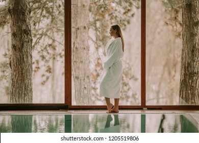 Pretty young woman in bathrobe standing by swimming pool
