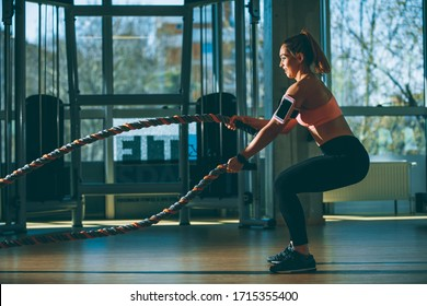 Pretty young woman with battle ropes exercise in the fitness gym